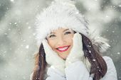 Beautiful Smiling Young Woman In Warm Clothing. The Concept Of Portrait In Winter Snowy Weather poster