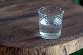 Glass Of Water As A Refreshment On A Small Wooden Table. Selective Focus Behind Blur And Bad Light. poster