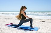 Woman Doing Yoga Exercise On Beach Rotated Low Lunge Or Ashwa Sanchalanasana Pose