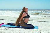 Young Woman Doing Yoga Exercise On Beach In Salamba Kapotasana Or Supported Pigeon Pose