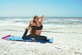 Woman Doing Yoga Exercise On Beach In Kapotasana Or Pigeon Pose Looking At Viewer