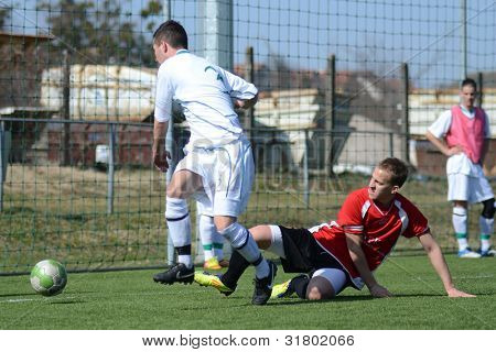 KAPOSVAR, HUNGARY - MARCH 16: Daniel Pager (in white) in action at the Hungarian National Championship under 19 game between Kaposvar (white) and Szentlorinc (red) on March 16, 2012 in Kaposvar, Hungary.