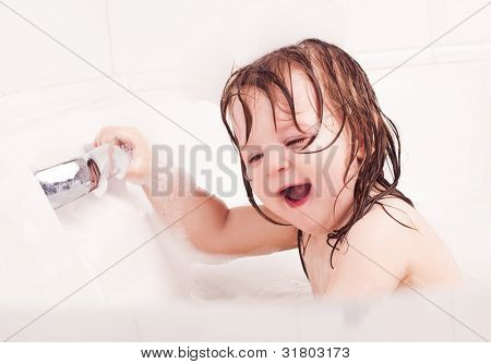 happy laughing one year old girl taking a bath with foam