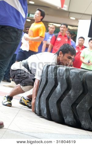 TOA PAYOH, SINGAPORE - MARCH 24 : Contender for Strongman Mohd Asri Abd Kadir attempts the 350kg times 6 flips in the Strongman Challenge 2012 on March 24, in Toa Payoh Hub, Singapore.