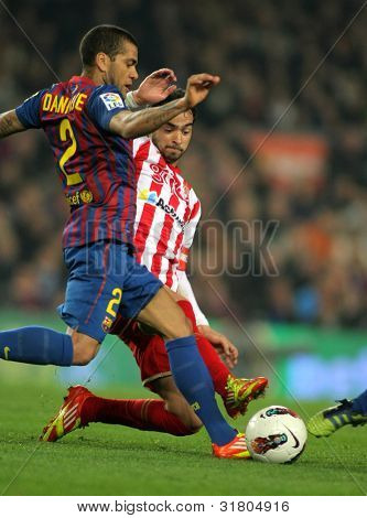 BARCELONA - MARCH 3: Dani Alves(L) of FC Barcelona vies with Nacho Cases(R) of Sporting Gijon in action  during the Spanish league match at the Camp Nou stadium on March 3, 2012 in Barcelona, Spain
