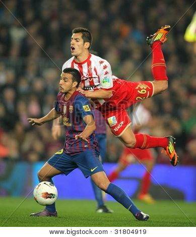 BARCELONA - MARCH 3: Pedro Rodriguez(L) of Barcelona vies with Pedro Orfila(R) of Sporting de Gijon during the Spanish league match at the Camp Nou stadium on March 3, 2012 in Barcelona, Spain