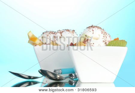 delicious vanilla ice cream with chocolate and fruits in bowls and spoons on blue background