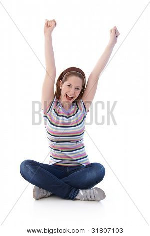 Young girl sitting on floor in tailor seat, stretching hands towards the sky, shouting happily.