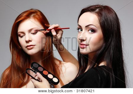 poster of Portrait of beautiful young redheaded woman with esthetician making makeup eye shadow