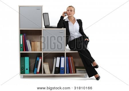 Woman sitting on a bookcase