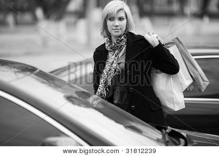 Young woman with shopping bags on a car parking