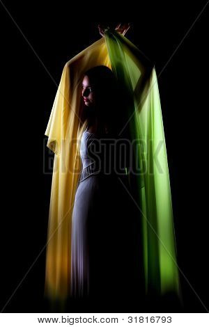 Green and yellow silky wings of voile fabric held by a young woman