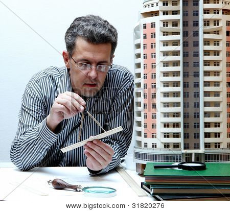 Architect with a breadboard model of a building