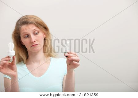 Woman Eyeing Incandescent Light Bulb