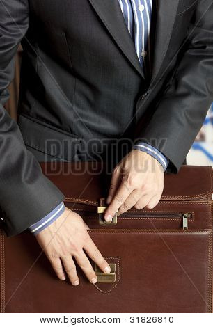 Businessman opening elegant brown leather briefcase