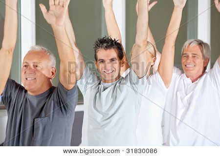 Happy senior people doing gymnastics exercises in gym