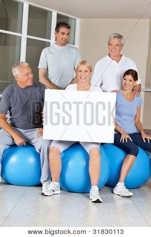 Senior citizens on gym balls doing advertising for fitness center