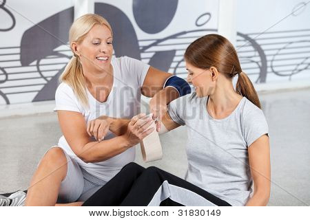 First Aid from fitness trainer in gym for woman with pain in her joints