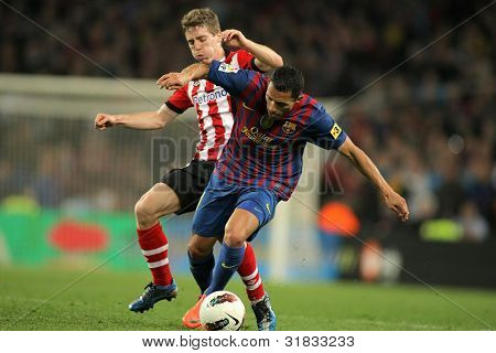 BARCELONA - MARCH, 31: Iker Muniain(L) of Athletic Bilbao vies with Adriano Correia(R) of Barcelona during the Spanish league match at the Camp Nou stadium on March 31, 2012 in Barcelona, Spain