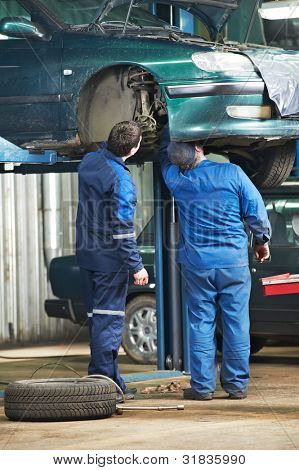 two motor mechanic diagnosing automobile car suspension before maintenance at repair service station