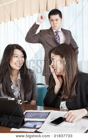 Manager watching his subordinate employees not working with anger