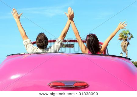 Freedom - happy free couple in car driving in pink vintage retro car cheering joyful with arms raised. Friends going on road trip travel on summer day under sun blue sky.