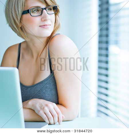 Portrait of a young woman pensively looking out of the window while sitting in front of her laptop