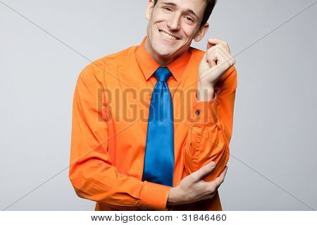 Young handsome happy man in orange shirt and blue tie.