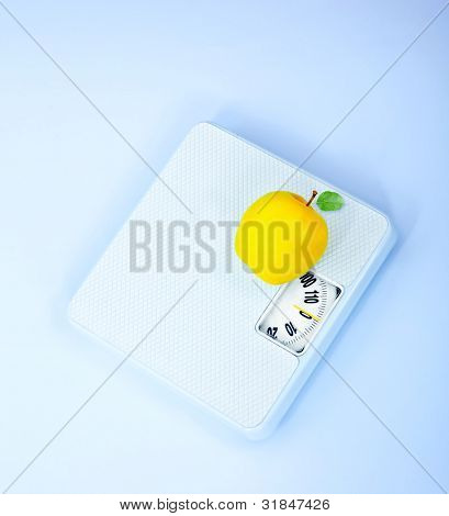 Scales and apple, body weight watching, conceptual image of dieting, calorie count, healthy lifestyle and shape control