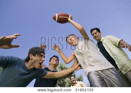Boy and Men Playing Football