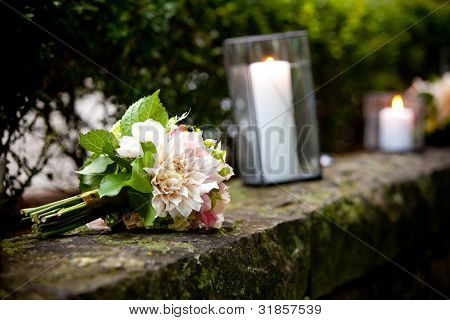 a brides wedding bouquet of flowers sitting on a wall