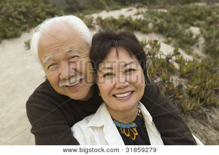 Mature Couple Sitting at Beach