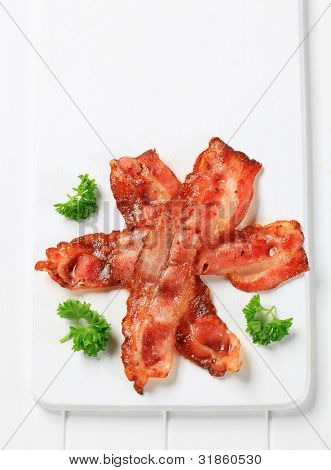 Hot sliced bacon like a star on a white rectangular tray