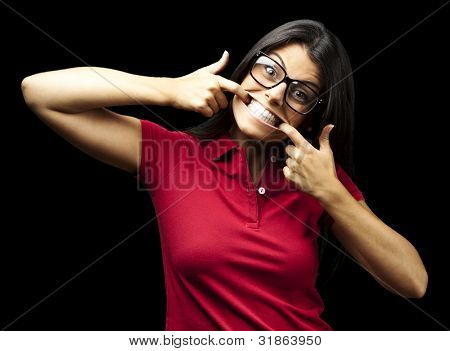 portrait of happy young woman doing a grimace over black background