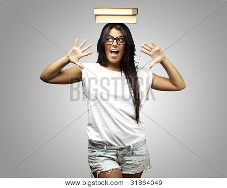 portrait of young woman holding books on her face over grey background