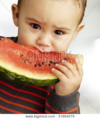 portrait of a handsome kid eating a watermelon