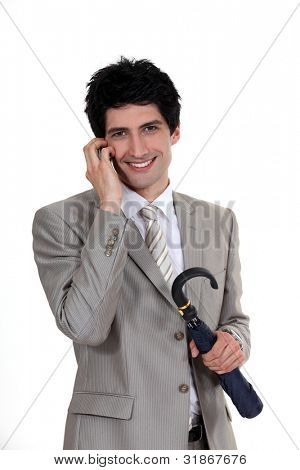 Businessman holding an umbrella and talking on a mobile phone