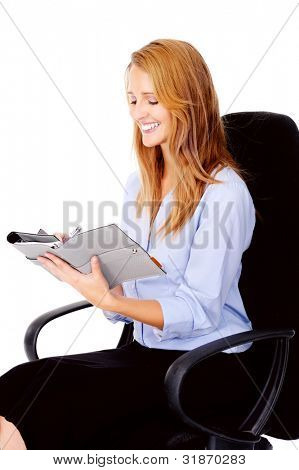 businesswoman writing in her organizer smiling and happy