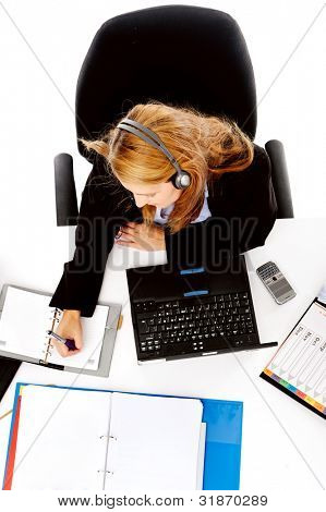 busy woman working at her desk. view from overhead of messy desk and multitasking women