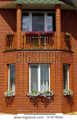 Windows of house with flowerpots on window-sills