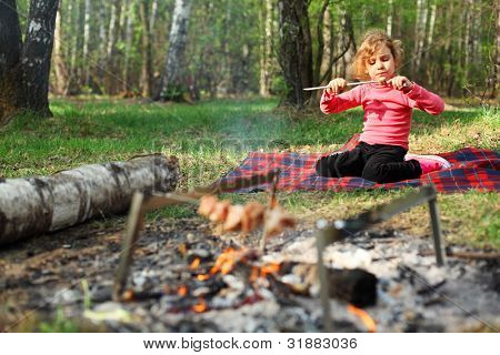 Girl sits near campfire with grill and barbecue and eats grilled shish kebab in forest