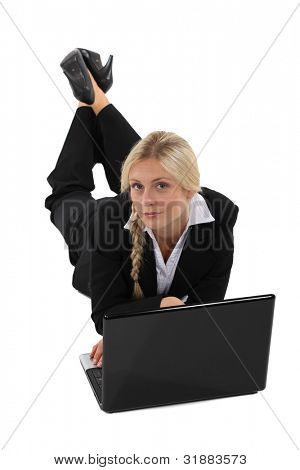 Businesswoman lying on the floor with her laptop
