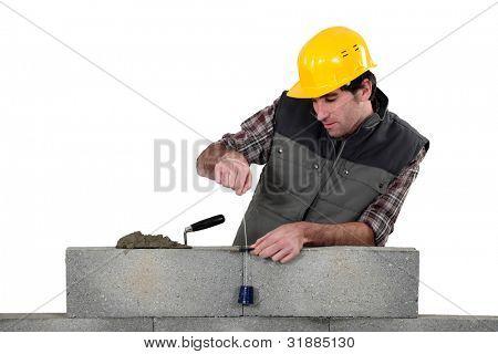 Tradesman using a plumb-bob