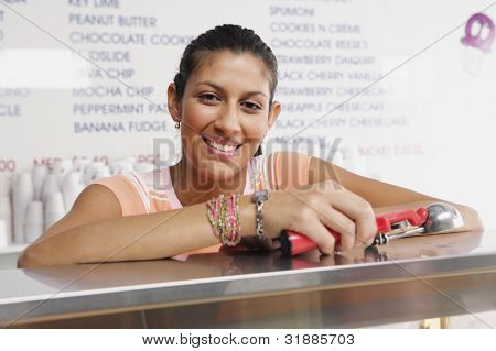Portrait of teenage girl working in ice cream shop