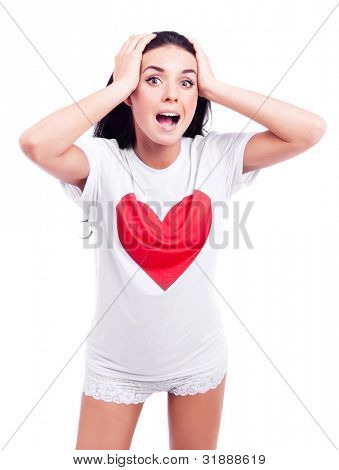 surprised young woman wearing a T-shirt with a big red heart and stretching hands to us, isolated against white background