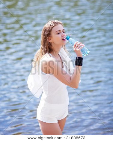 beautiful young  sporty woman running in the park on a warm summer day and drinking water