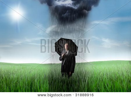 Sad senior businessman on a green meadow with downpour over him and sunny sky in the background