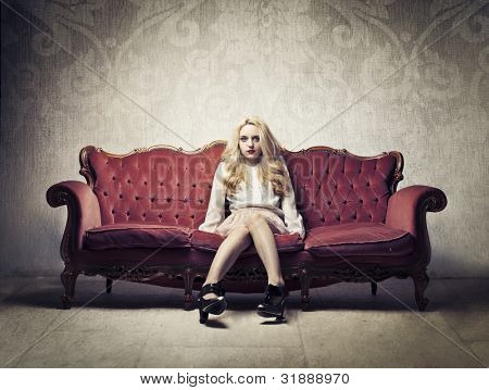 Rich elegant woman sitting on a velvet antique sofa
