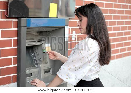 Young woman withdrawing money from a cashpoint