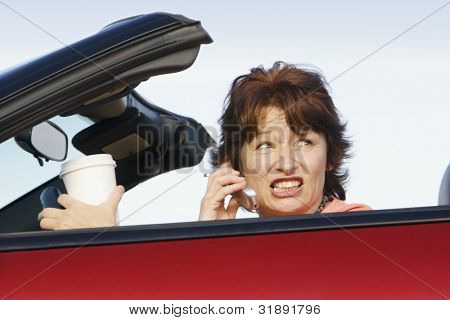 Stressed woman driving convertible while talking on cell phone
